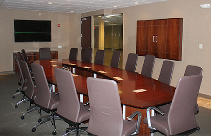 Custom wood racetrack conference table with matching wall cabinet and credenza in a Milwaukee meeting room