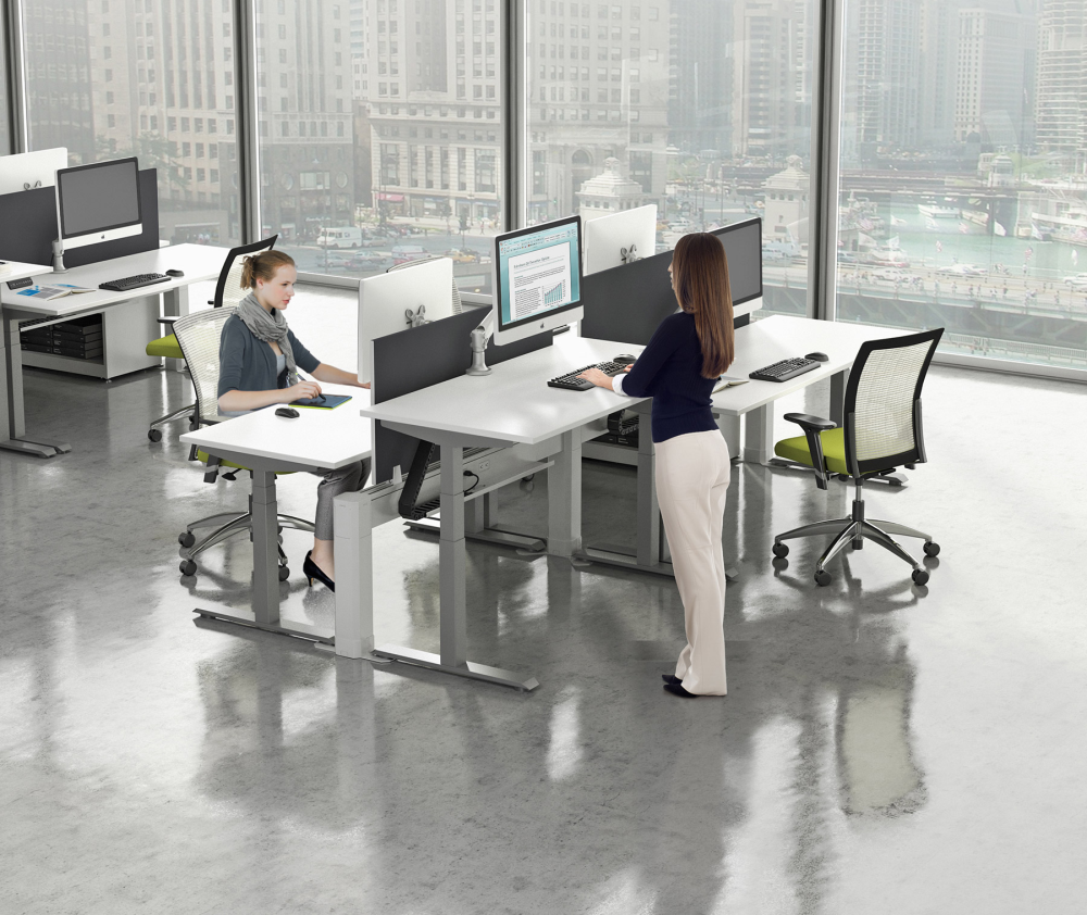 Cluster of 4 adjustable height office tables with office workers sitting and standing