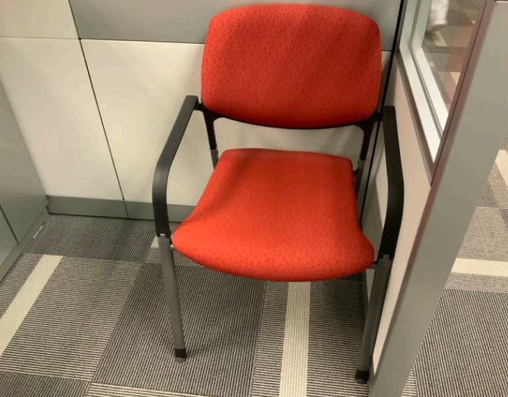 Used Steelcase Vecta stacking chair with grey legs and orange fabric seat